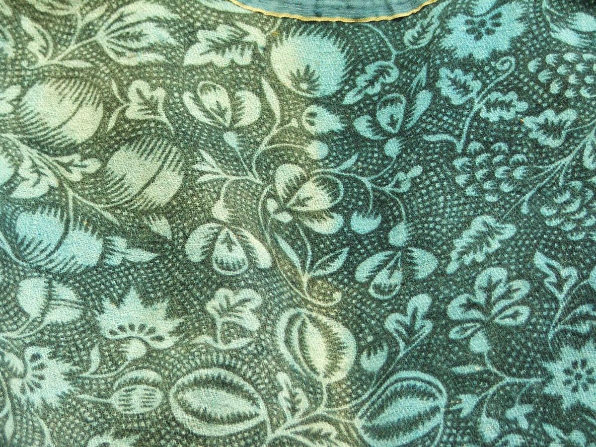 Mønster på liv : Mørk grøne blomar og blad på lys grøn og mørk grøn/lysgrøn-rutet botn. Noko som liknar drueklasar, fleire typar blad og blomar.