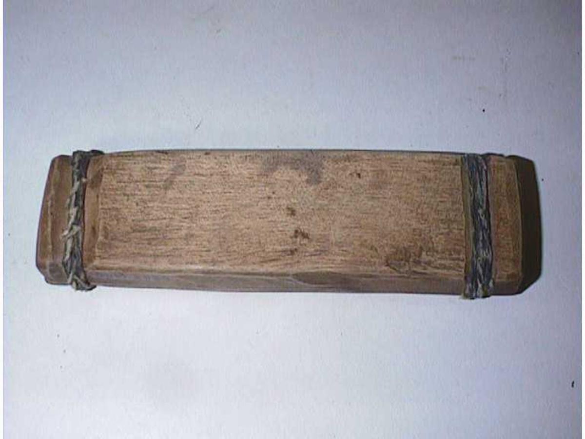 Eitt utskore trestykke med vegger i lengda, eitt flatt stykke som lok. Ope i endane. Bundne saman med tråd (Bekatråd?)
