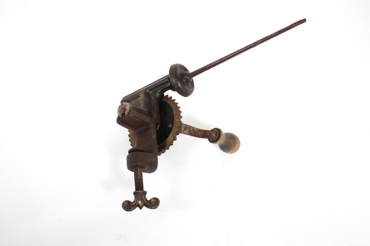 Tannhjul med sveiv kopla mot ei tynn stang som tråden blir vinda opp på. Skrue til feste på bord