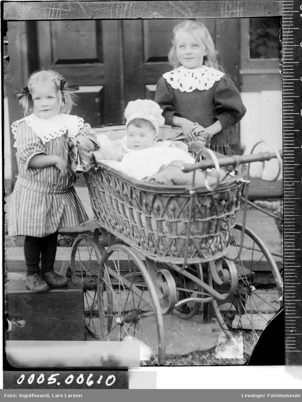 Portrett av tre barn og en barnevogn.