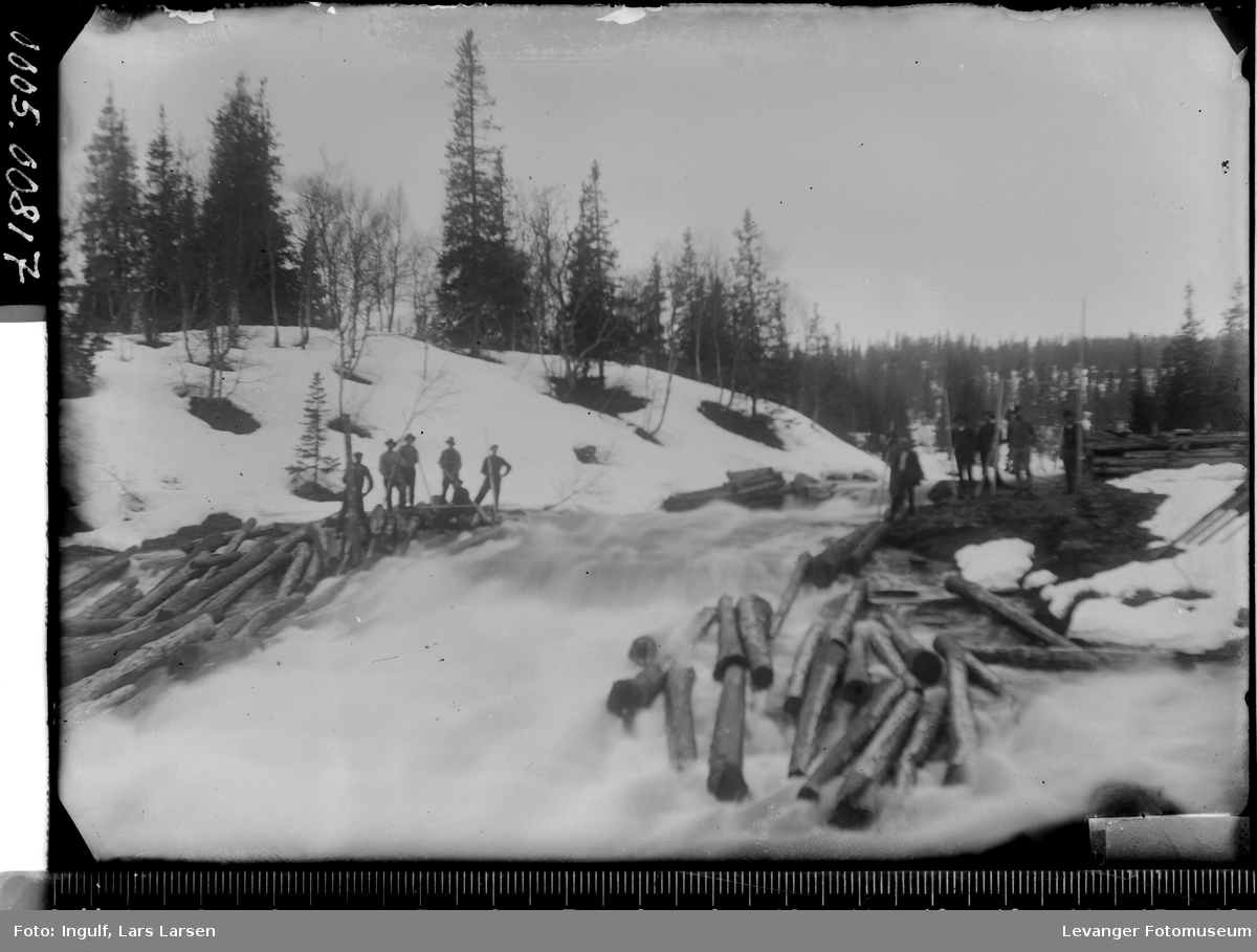 Fløting av tømmer ned en elv vinterstid.