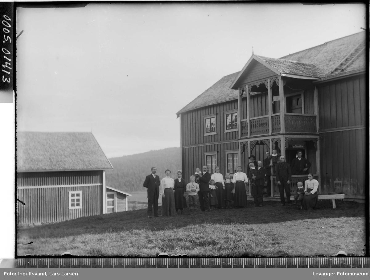 Gruppe av menn, kvinner og barn utenfor et hus.
