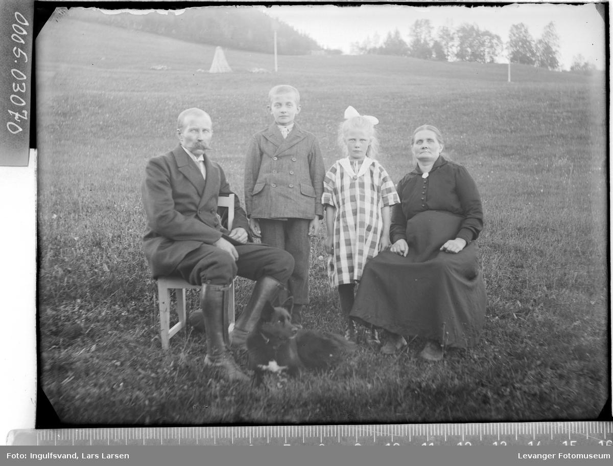 Gruppebilde av kvinne, mann og to barn i helfigur.