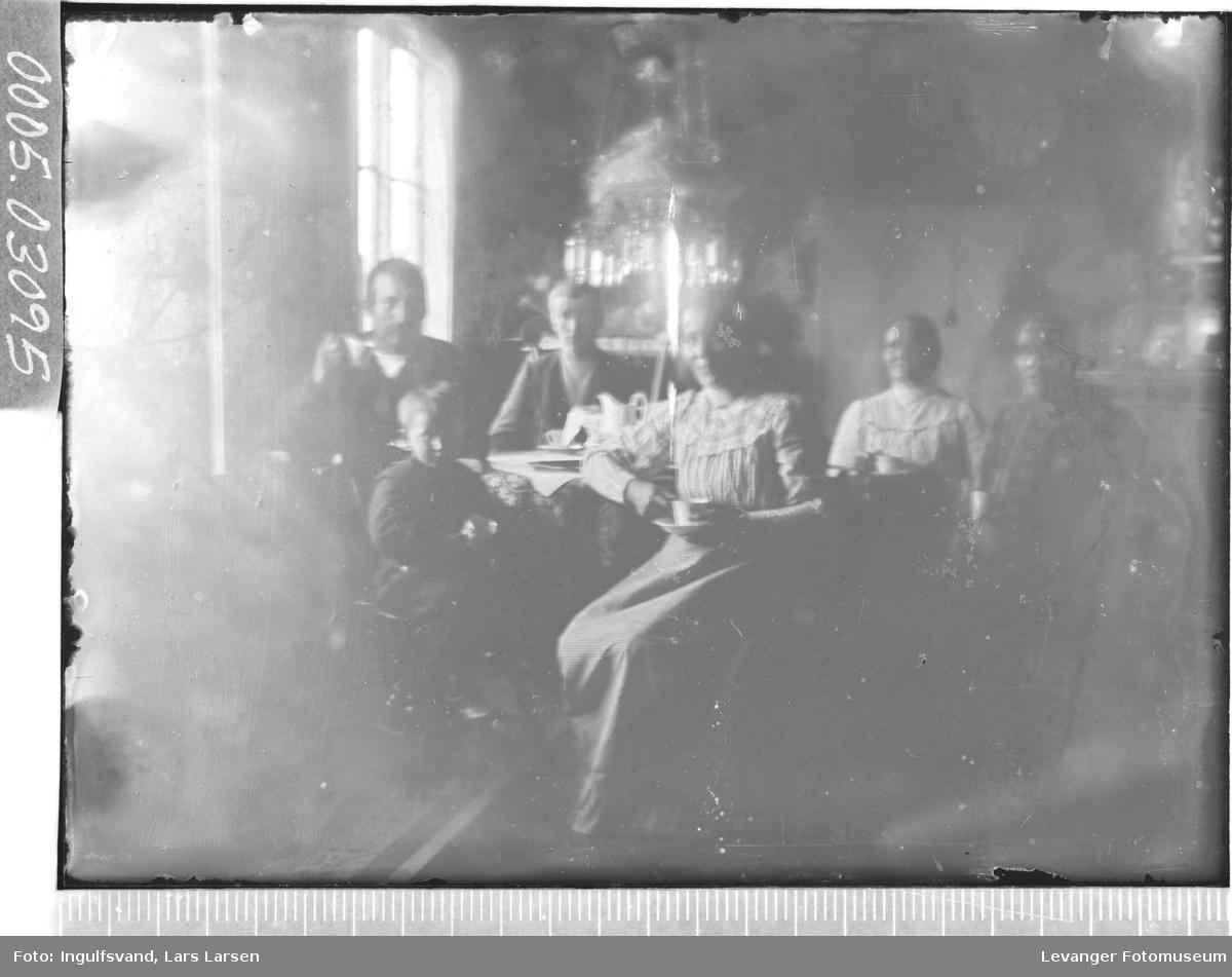 Gruppebilde av tre kvinner, to menn og et barn rundt et spisebord.