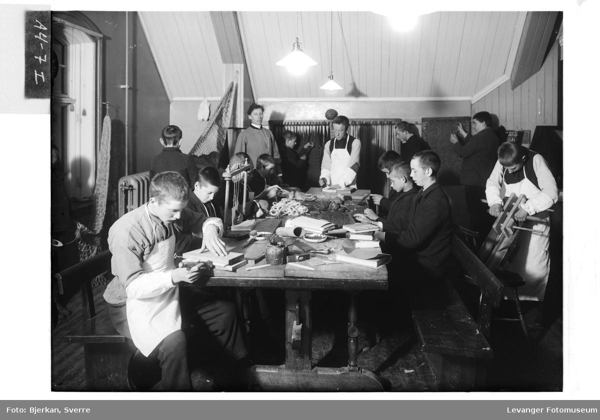 Elevene på Røstad skole lærer seg bokbinderi, garnknyting og trolig teging eller fletting av siv eller hamp.
