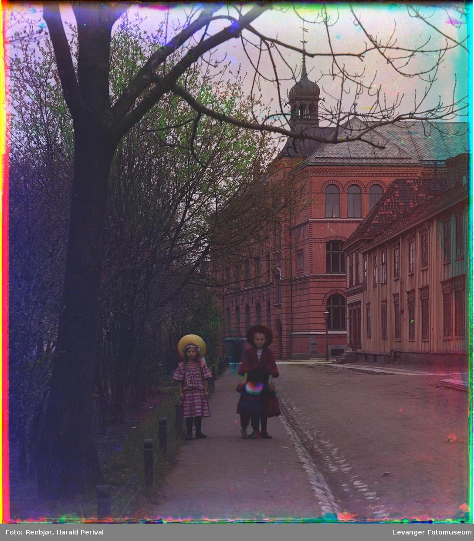Tre barn går langs en gate i Trondheim. Bakenfor var Trondheim borgerlige realskole, senere Gerhard Schønings skole, nå Thora Storm videregående skole.