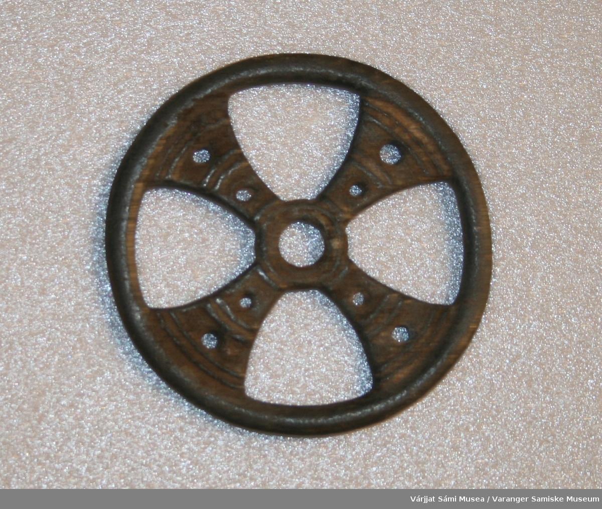 """Rundt belteanheng av grått metall. sannsynligvis tinn/bly. Ser ut som et hjul delt opp i fire """"rom""""."""