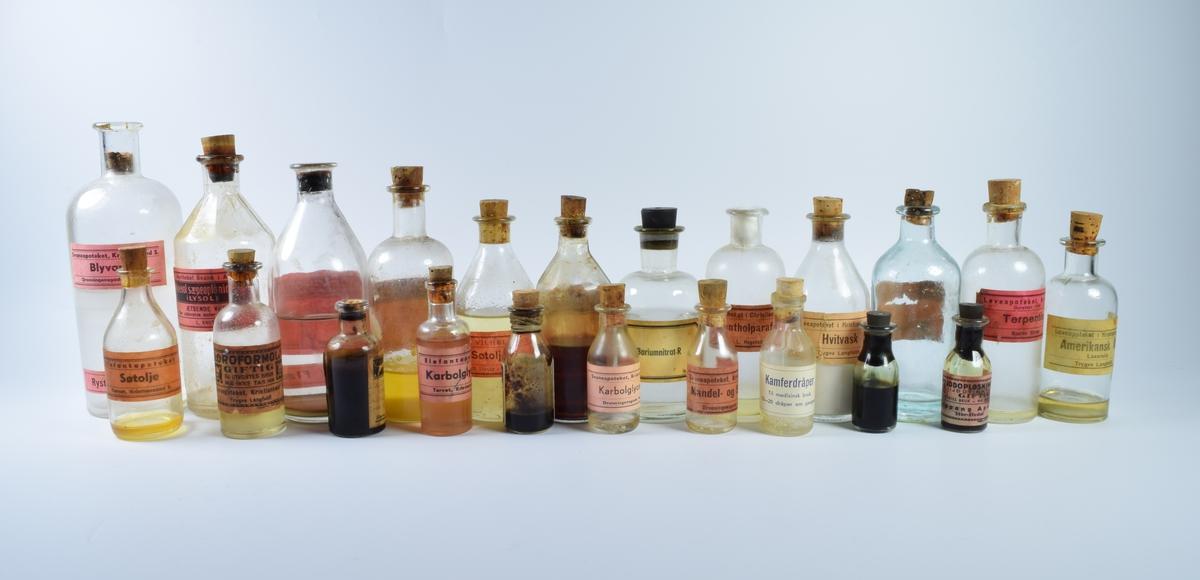 """22 flasker i forskjellig størrelse i klart glass. Mange av flaskene har rester av det opprinnelige innholdet.  a: Stor flaske med blyvann. Korken er brukket av og sitter fast nederst i flaskehalsen. Etiketten er rosa med sort skrift.  b: Tom flaske med mangekantete skuldre. Etiketten er rosa med sort skrift og bilde av en hodeskalle. Flasken har inneholdt """"Kresol sæpeopløsning""""  c: Reseptflaske fra Løveapoteket med falmet, rosa etikett. Navnet på reseptinnehaveren er revet bort. Flasken har inneholdt """"Steril glycerin"""".  d: Flaske halvfull med hvitvask. Etiketten er gul med sort skrift.  e: Reseptflaske fra Løveapoteket med rester av en gul væske i bunnen. Etiketten er rosa med sort skrift.  f: Nesten full flaske med søtolje. Etikett er rosa med sort skrift.  g: Reseptflaske fra Løveapoteket som er halvfull av en brun væske. Etiketten er rosa med sort skrift.  h: Flaske med sort kork av gummi. Flasken er nesten full og skal inneholde Braiumnitrat-R.  i: Tom flaske uten kork, merket """"Mentholparafin"""".  j: Reseptflaske fra Løveapoteket som er halvfull med en klar væske. Korken er brukket av og sitter fast inne i flaskehalsen. Etiketten er rosa med sort skrift.  k: Flaske med rester av terpentin i bunnen. Etiketten er rosa med sort skrift.  l: Flaske med rester av amerikanskj olje i bunnen. Etiketten er hvit med sort skrift.  m: Liten flaske med søtolje fra Elefantapoteket. Det er rester av innholdet i bunnen. Etiketten er rosa med sort skrift.  n: Liten flaske med to hodeskaller på etiketten. Det er rester av en klar væske i bunnen, samt en kork som har falt ned. Flasken inneholder """"Kloroformolje"""".  o: En liten, nesten full reseptflaske fra Løveapoteket. Den øverste delen av korken er brukket av. Etiketten er hvit med blå og sorte border.  p: En nesten full, liten flaske med karbolglyserin fra Elefanapoteket. Etiketten er rosa med sort skrift.  q: Liten reseptflaske med rester av en mørk væske i bunnen. Rundt flaskehalsen er det surret to gummistrikker. Etiketten er hvi"""