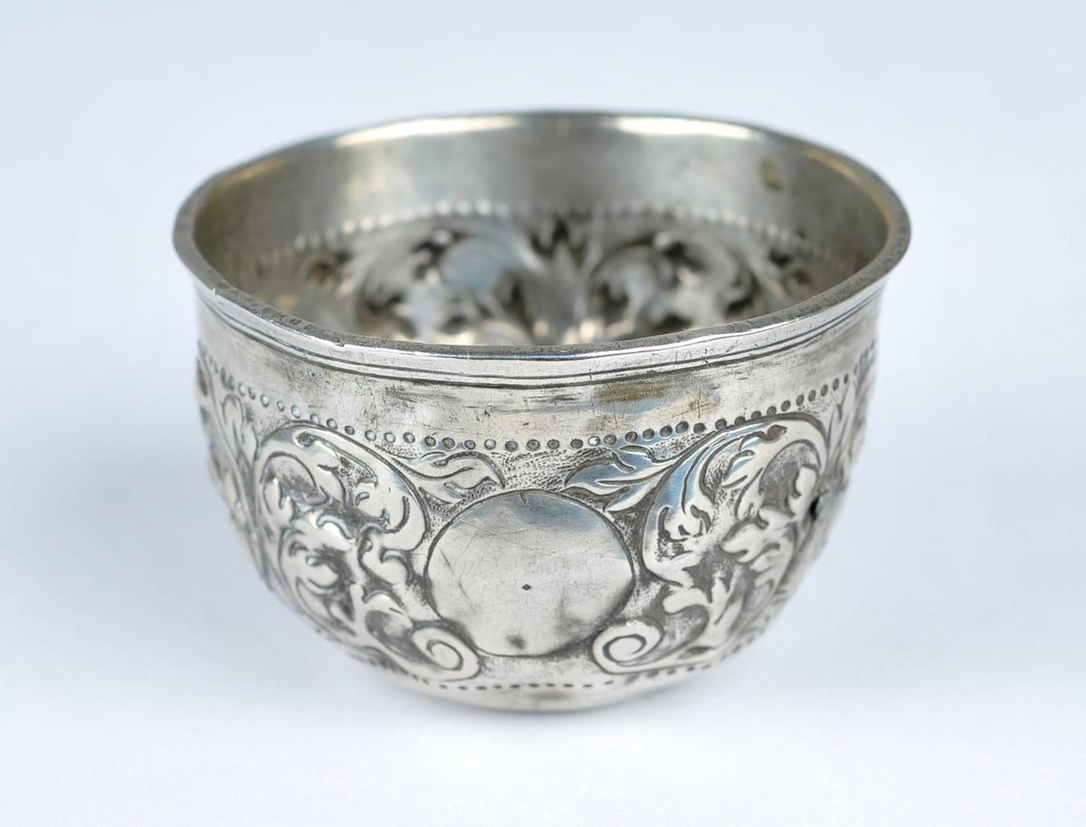 Halvkuleforma sylvbolle.Siselera utvendig, C-motiv. I botnen er det lodda inn ein dansk-norsk mynt, år 1704.