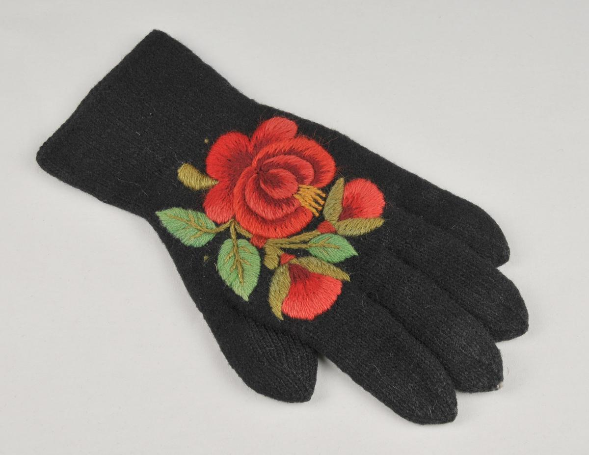 Fingervott i svart ullgarn med rosesaum. Motivet er ei stor rose og to knoppar med grøne blad.