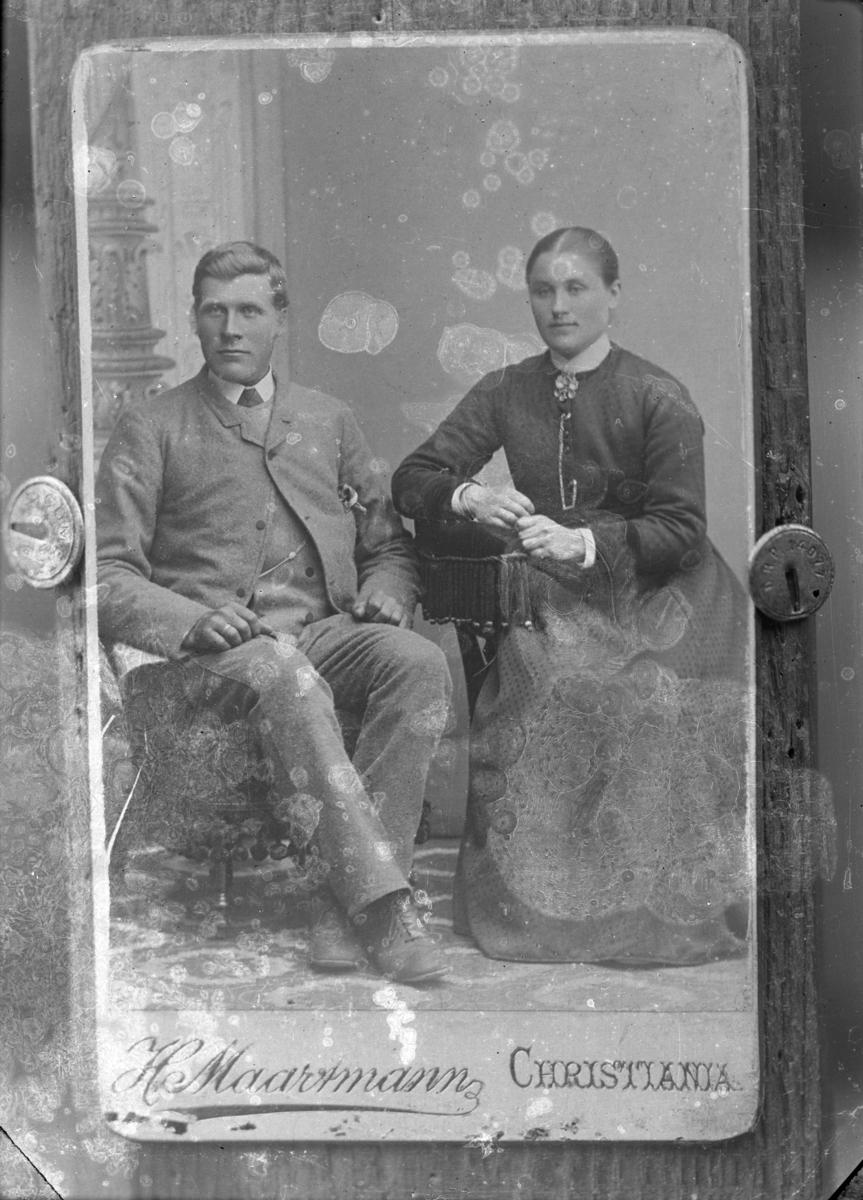 Fotografi av fotografi, med påskriften Christiania og uklar fotografsignatur . Kvinne og mann sittende i hver sin stol