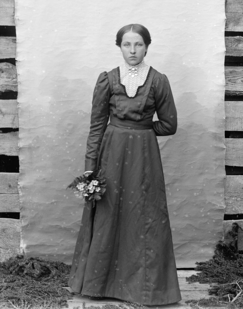 Kvinne i helfigur med blomsterbukett, kledd i mørk kjole. Lerret på husvegg som bakgrunn