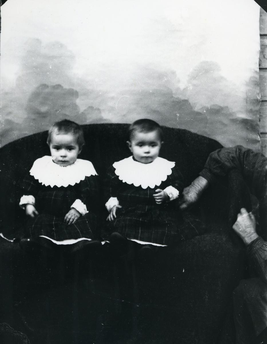 To spedbarn kledd i rutete kjoler og hvite krager