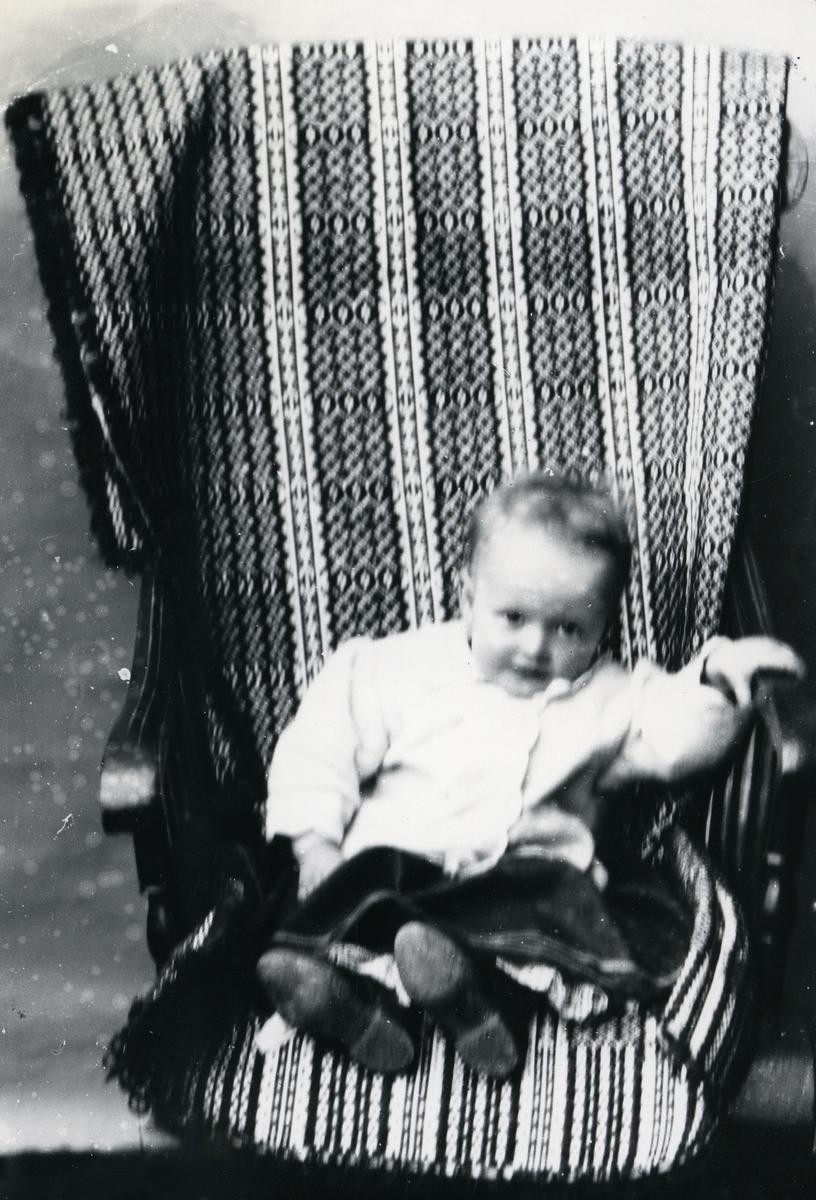 Spedbarn i gyngestol med mønstret pledd