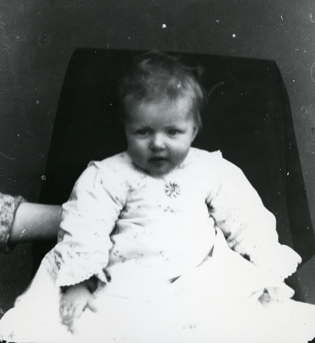 Spedbarn kledd i lys kjole, i stol med lerretbakgrunn