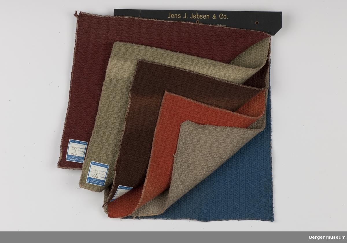 Prøvebok med seks prøver. Kraftig møbelstoff. Metervare. Ensfarget. Mønstret som et slags flettemønster som danner striper i stoffet.