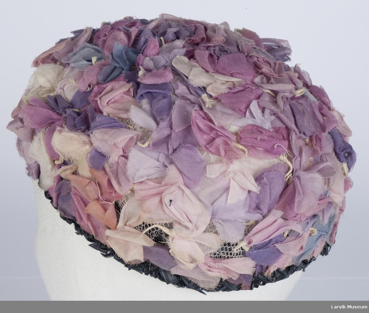 Form: pull av gas, dekket med små stoffblomster i rosa og lilla nyanser, mørkblå strå-rysje langs kanten, der et sort ripsbånd er satt mot vrangen, hvit fórsilke og strikk i nakken
