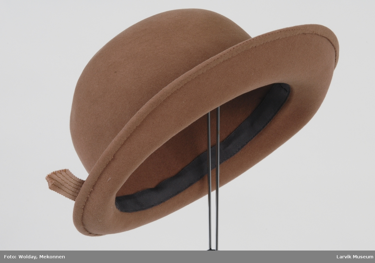 Form: Stor pull, liten brem. Bånd med flat sløyfe rundt pullen.