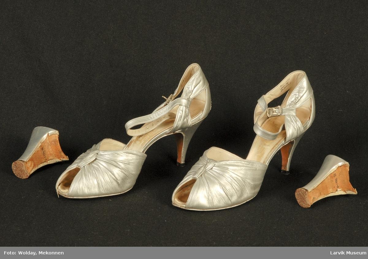 Form: Sandal med høy smal hel, tidligere har skoen hatt en tykkere hel, denne følger med. Tett i en del av helen, her er også en rem rundt ankelen. Denne blir festet med en strassspenne. Fronten over tærne er snurpet sammen og bundet sammen på midten.