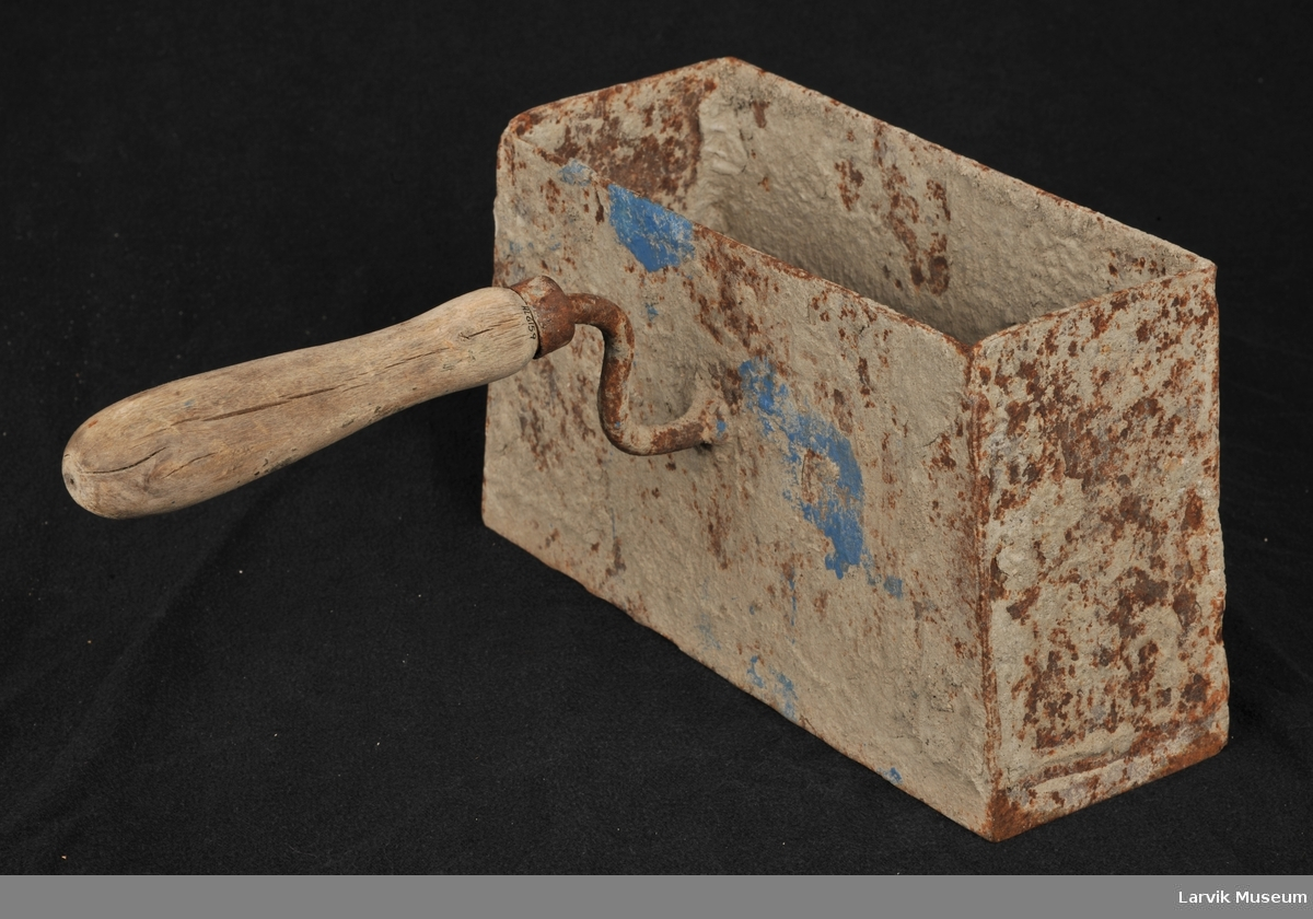 Firkantet avlang mursteinsform med håndtak festet midt på langsiden