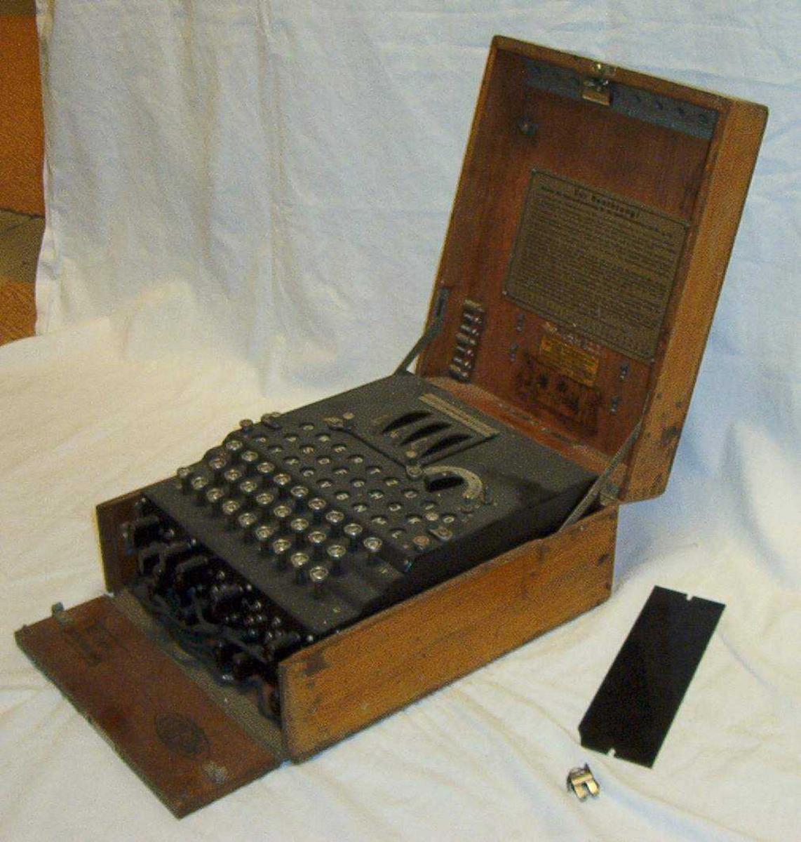 Sort krypteringsmaskin i rektanglær brun trekasse med lokk.