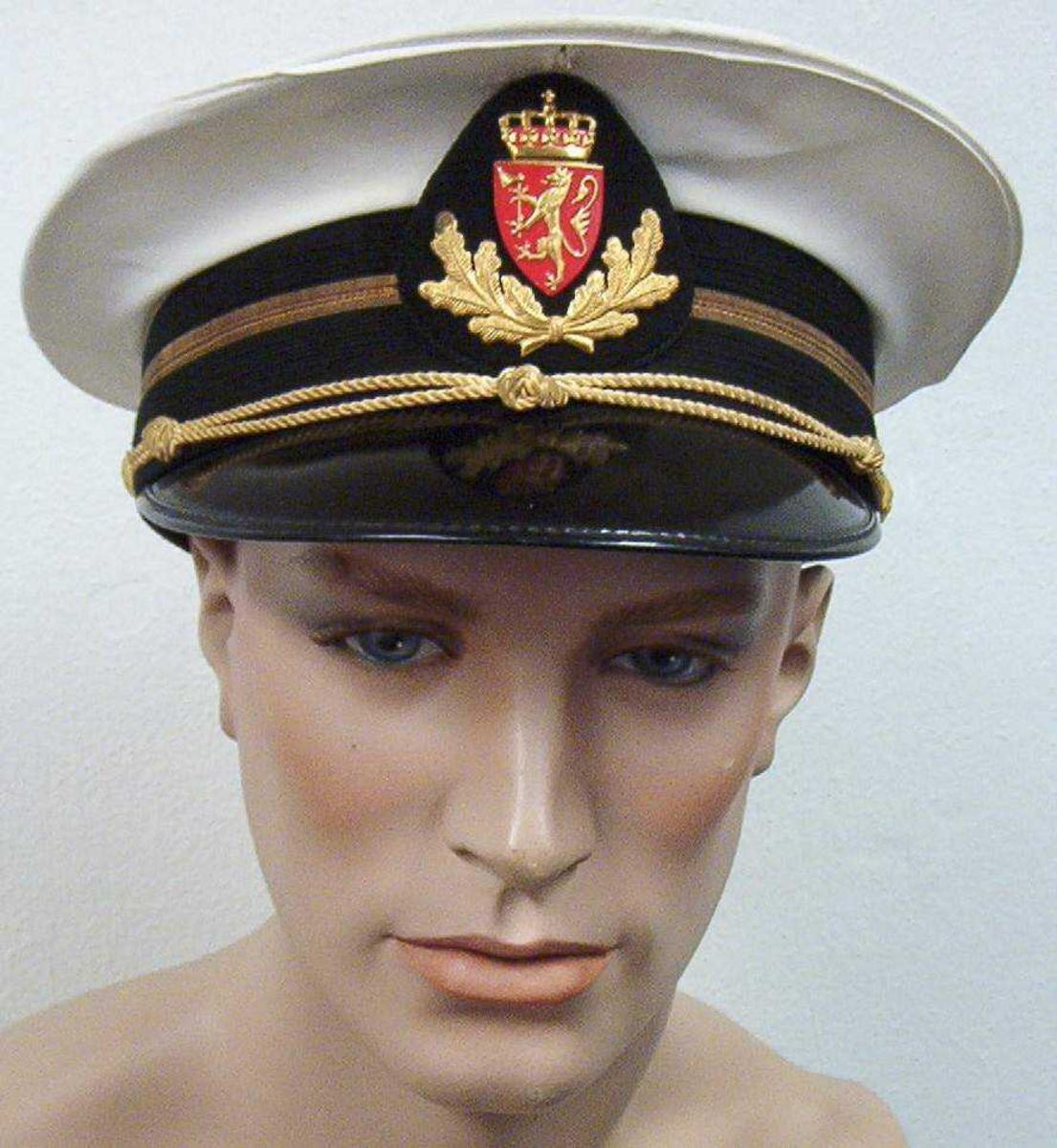 Hvit uniformslue med sort luebånd med en gullstripe, sort lakkskjerm og gulltresse. Luemerket er riksvåpenet med eikegreiner på dråpeformet stoffmerke.