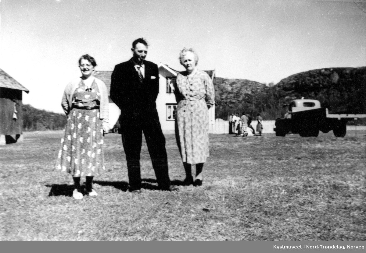 2 eldre Ukjente kvinner og en mann på gårdstun