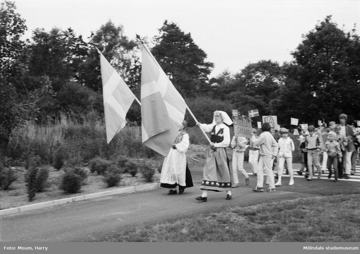 """Nationaldagsfirande i Kållered, år 1984. """"Brattås och Livereds skolor på väg mot Ekenskolan tillsammans med daghems- och lekskolebarn.""""  För mer information om bilden se under tilläggsinformation."""