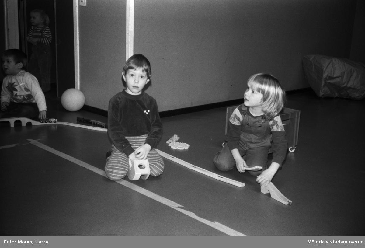 Öppen förskola på Almåsgården i Lindome, år 1983. Pojke och flicka leker med modelljärnväg.  För mer information om bilden se under tilläggsinformation.