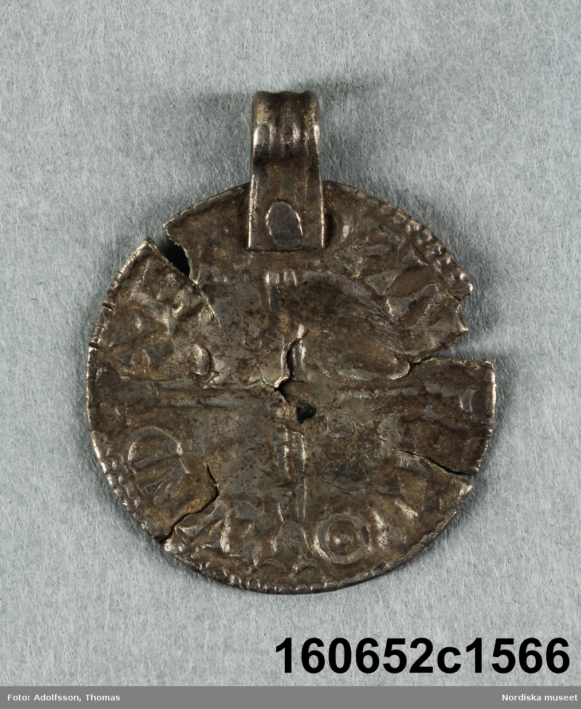 1 anglo-saxisk penning. En silverögla är färstad vid myntets kant.