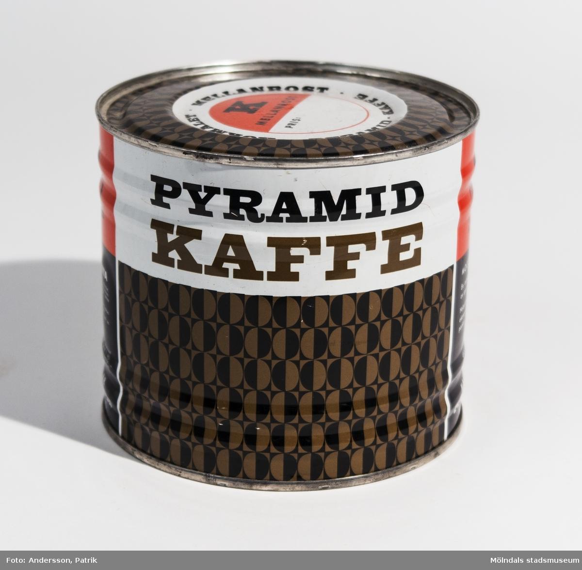 """Kokmalet - Mellanrost - Pyramid - Kaffe En oöppnad kaffeburk i plåt från 1950-talet.  På burken finns texterna:  """"Moccablandning En expertprovad lyxblandning av speciellt utvalda kaffesorter. Helautomatiskt aromrostat, ekonomimalet och högvaciumpackat.  Öppna burken - känn doften... drick och n-j-u-t ett verkligt gott kaffe.  Pyramid kaffe Piggar upp, smakar gott - ett kaffe som k-ä-n-n-s""""  Kaffeburken är flerfärgad, i färgerna svart, vit, brun och orange."""