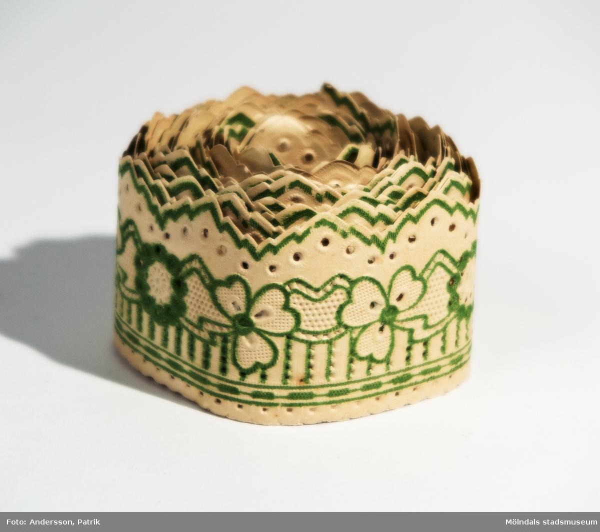 Hyllremsa från 1900 - 1925 tillverkad av Pappersvaror en gros. som låg på Linnégatan i Göteborg. Frithof N Göthberg född 1878, arbetade troligtvis på Pappersvaror en gros.  Mönstret på hyllremsan går i grönt och föreställer bland annat kransar.