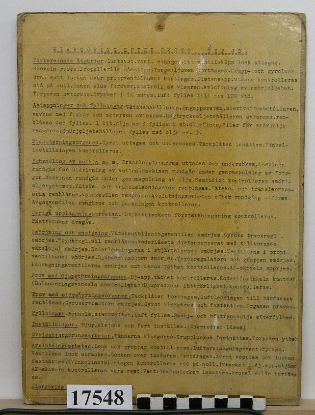 Skylt av skiktlimmat papper, på båda sidor klistrat papper med maskinskriven text. Texten behandlar klargöring efter skott med torped typ JB samt periodisk tillsyn av upplagd torped. Fernissad och gul. Hål för upphängning.