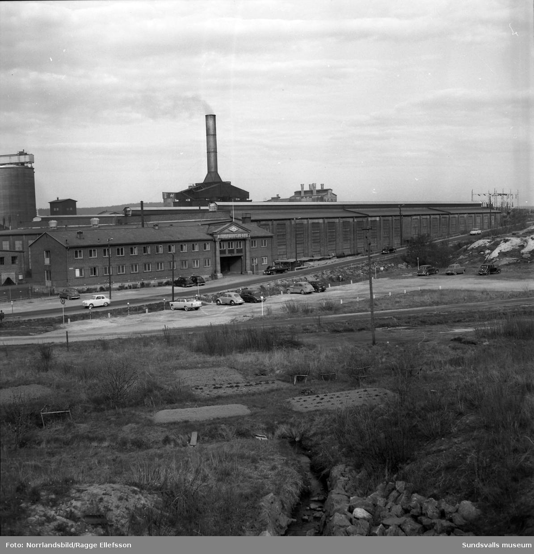Aluminiumkompaniet (Kubal), exteriörbilder sett från järnvägen. I förgrunden syns kvarvarande delar av trädgårdar och odlingar på området där E4 numera (2015) ligger.