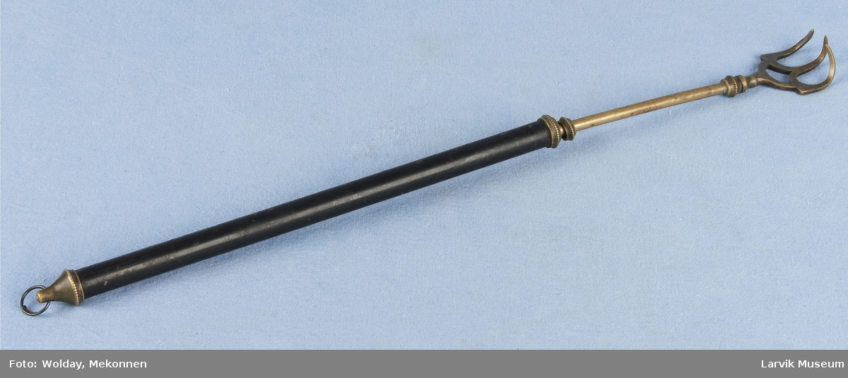 "Form: Langt sylinder formet håndtak, som har en fin avslutning i begge ender. I den ene enden fortsetter den i en smalere pinne som igjen ender i en ""gaffel"" ""Hånd"""