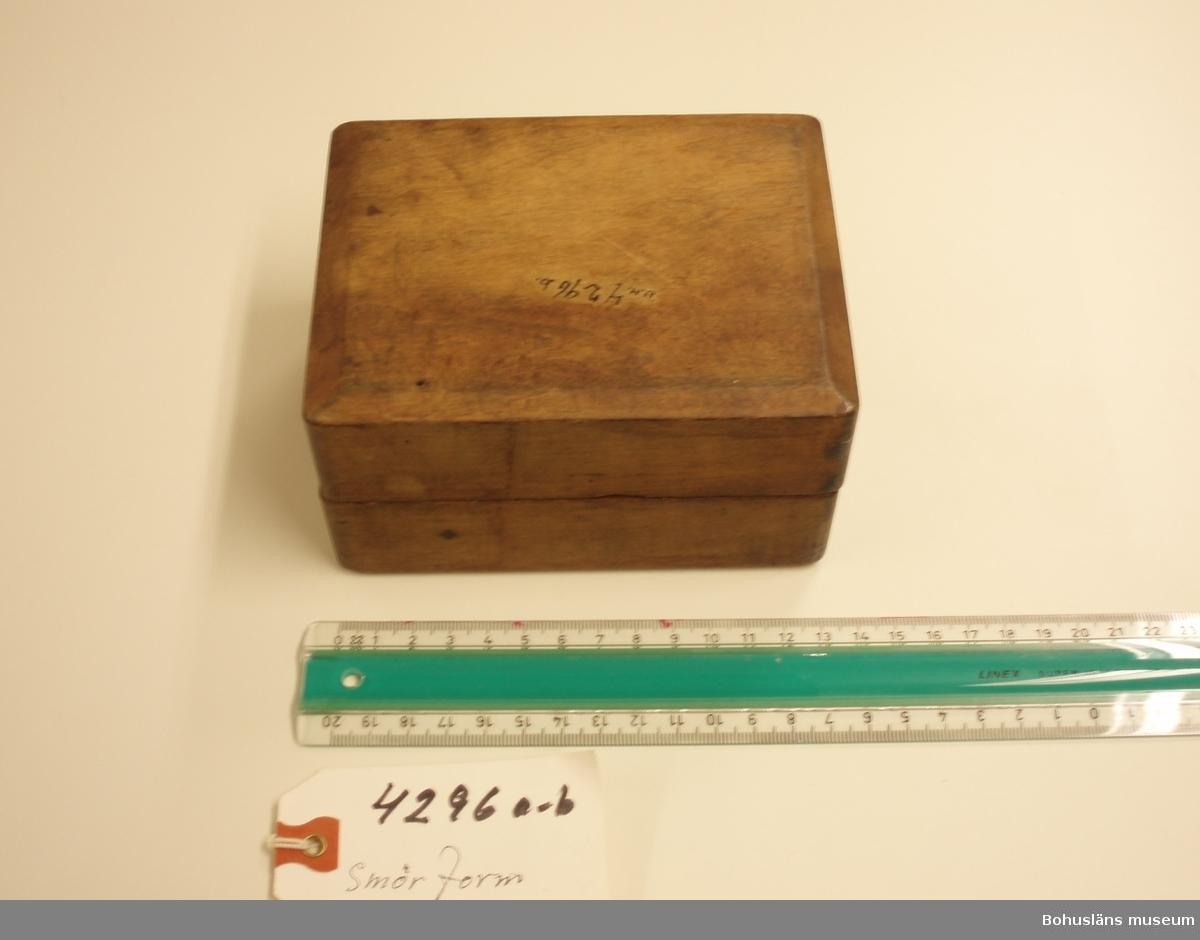 Tvådelad smörform som formar smöret till ett liggande lamm.  Ur handskrivna katalogen 1957-1958: Smörformare I 2 delar, a-b, mått (hopsatt)13,5 x 10,3 x 7,8 cm, av trä, omålat; form till höna el. dyl. Hel.