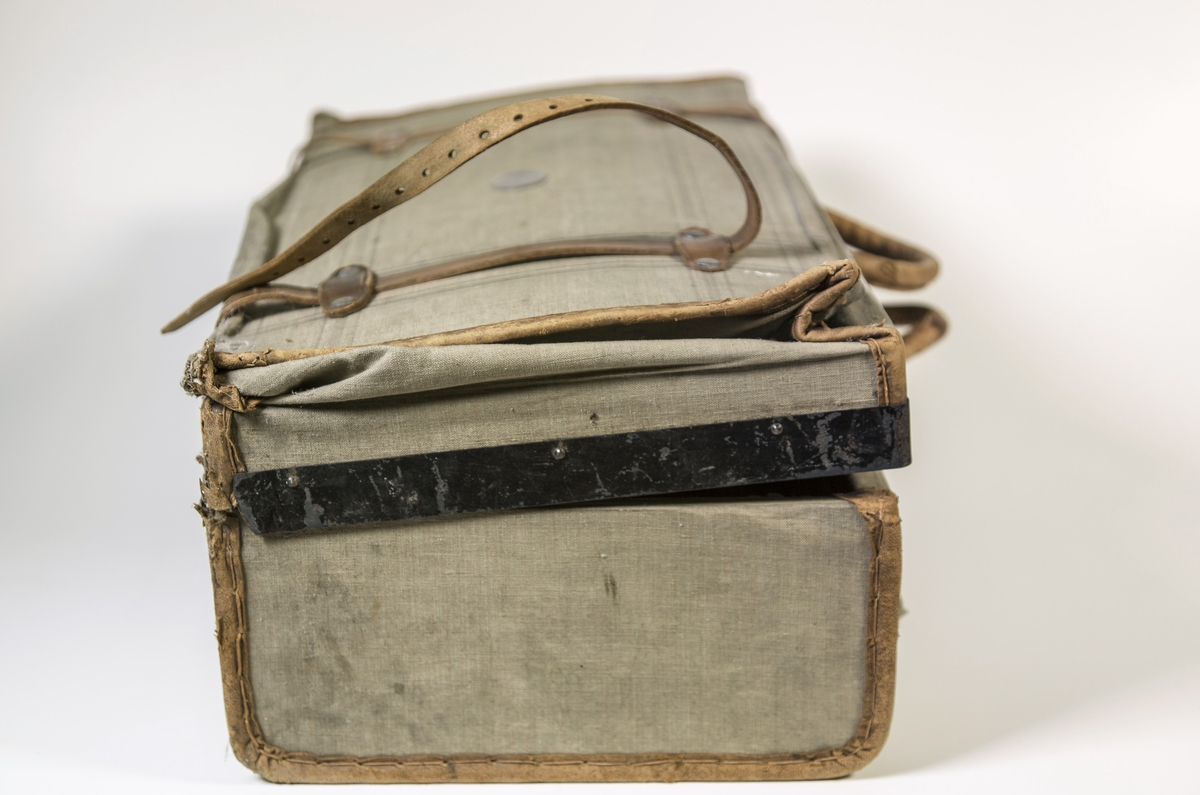 Tekstil på papp med lærforsterkninger, sort metallås m/lærrem på hver side. To håndtak. Rester etter plombering.