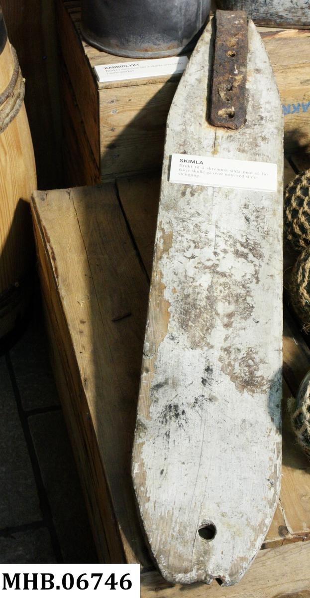 Avlang skimle skåret ut av ett trestykke. Øverst ett gjennomgående hull til tau. Nederst ett rektangulært jernbeslag som hadde funksjon som lodd. Skimlen ble brukt til å skremme silda til å bli inni noten under fiske.