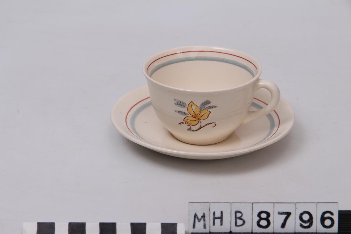 Dekorstripe på tefatet og langs munningen på koppen innvendig. Blomst med tre blader fremme og bak på koppen.