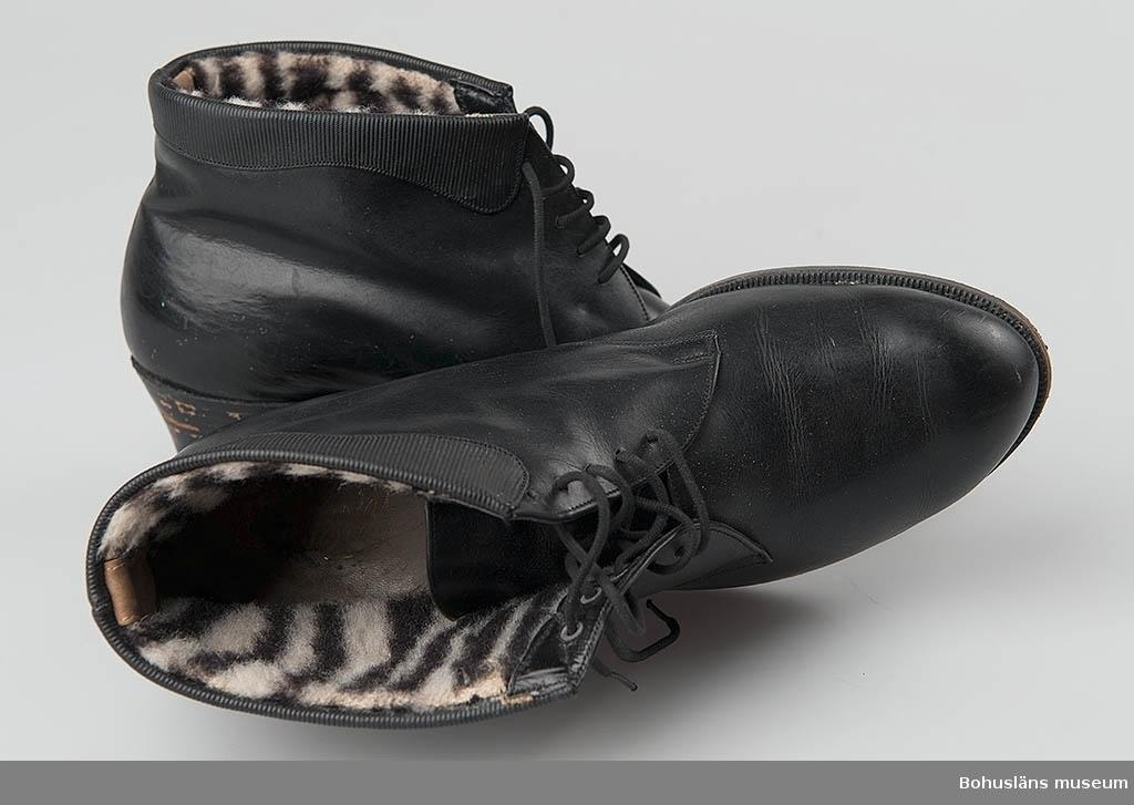 Svart läderkänga för kvinna. Halvhög läderklack, vit-svartrandigt konstmaterialfoder, snörd fram. Räfflad gummisula sekundärt lagd på lädersula.