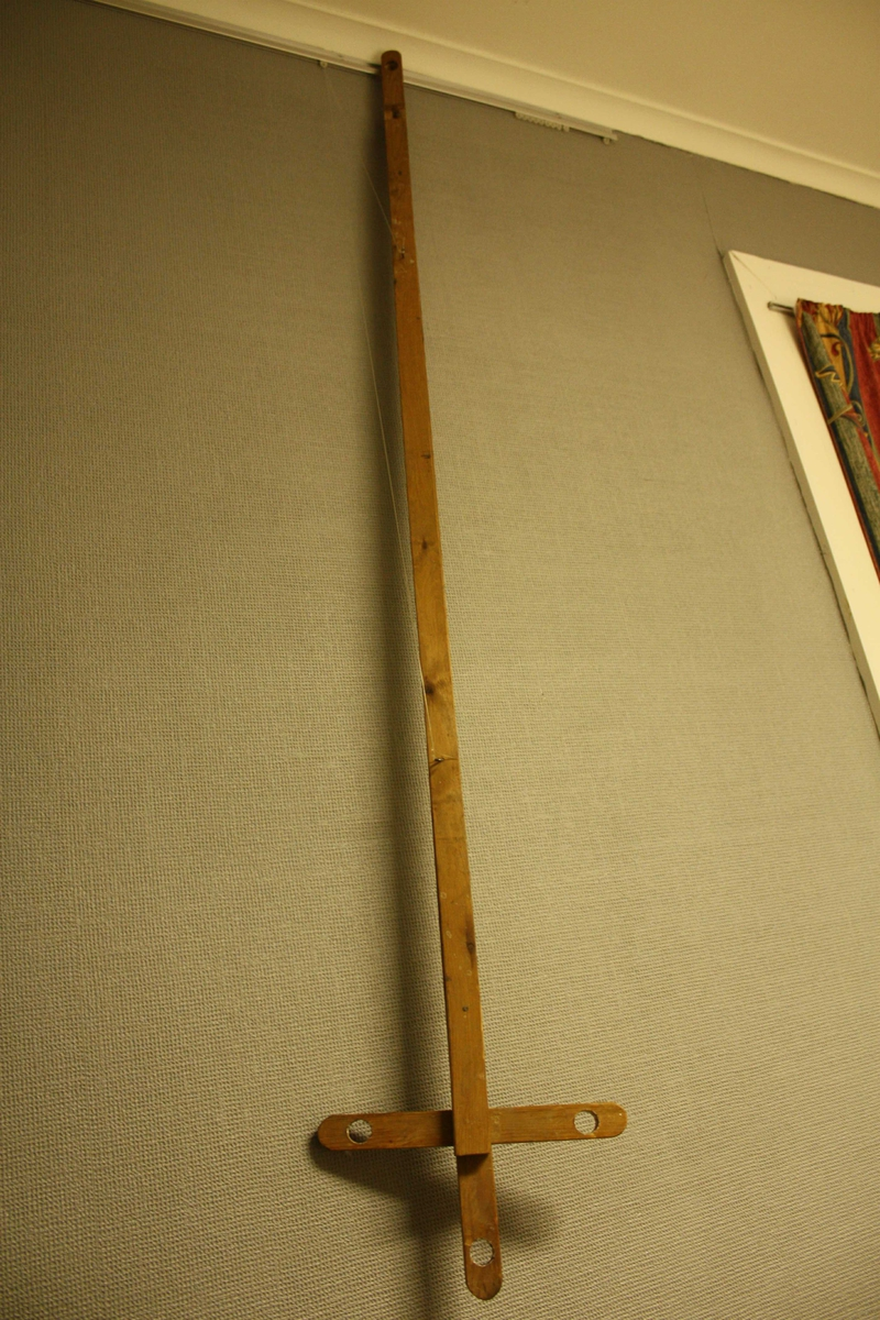 Langt, utrekkbart stag, formet som et kors i endene hvor det er boret tre gjennomgående hull for stearinlys.