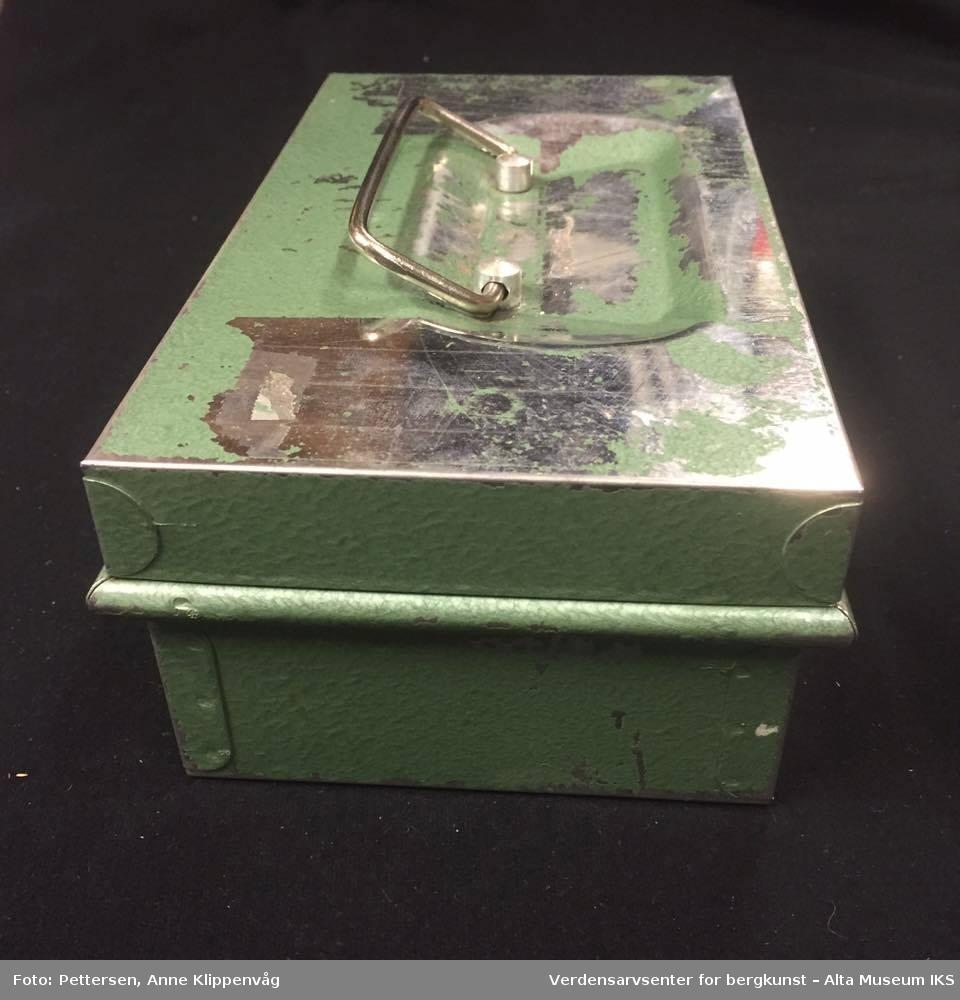 Rektangulert grønnfarget skrin i metall. På lokkets overside er det et bærehåndtak i metall. På fremsiden av skrinet er det et nøkkelhull uten nøkkel.  Inne i skrinet er det en sort plastikkorganisator der det ligger tre ulike matbonghefter for personalet ved Jansnes Psykiatriske Sykehjem.