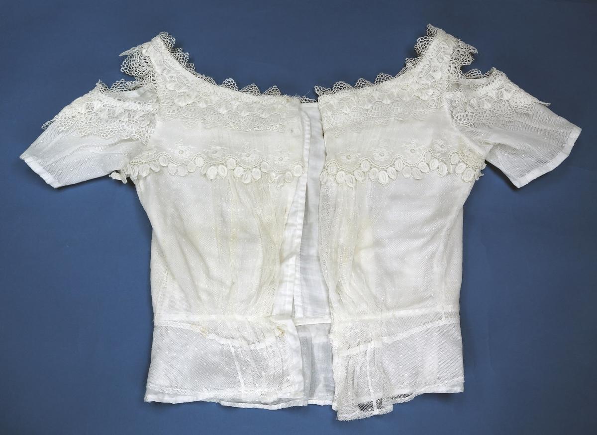 Bluse med korte ermer og blondepyntet åpning på skuldrene. Blusen er av tynt lerretsvevd bomullsstoff, med et tyllstoff over som er dekorert med blonder (nupereller?) over dette omkring bryst- og skulderparti. Blusen er innsvingt i livet, og har skjulte hekter