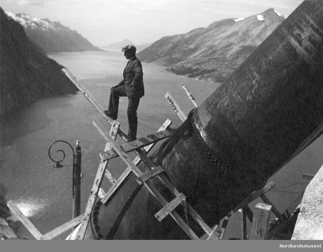 Utsyn mot Glomfjorden. Rørgata i forgrunnen. Mann (Bernt Lund) poserer på stillas på rørgata.