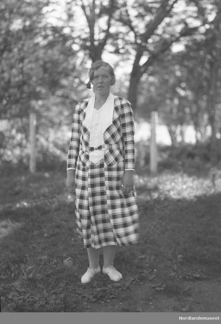 Portrett av kvinne. Pent kledd. Trær i bakgrunn.