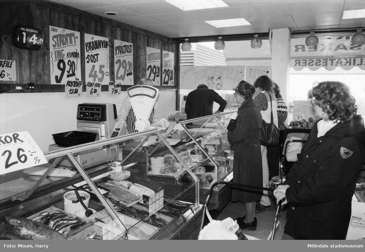 Ny fiskaffär, Fiskhörnan, på Hagabäcksleden i Kållereds centrum, år 1983. Christer Augustsson och Christina Sjöbring betjänar kunder.  För mer information om bilden se under tilläggsinformation.