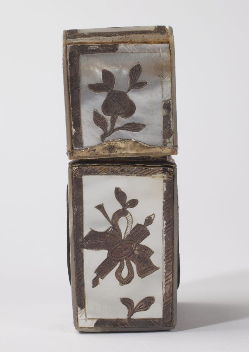 Necessaire av perlemor med hengslet lokk. Dekortert med malte medaljonger med amoriner. På ene siden står det NECESSAIRE og på andre DETOILLETE som del av dekoren. Inneholder en parfymeflakong, en pinsett, tre små spatler, og en gjenstand som består av tre bein- eller hornplater.