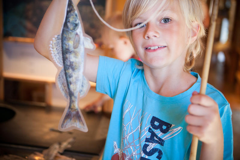 Glad gutt har fått fisk inne på Besøkssenter våtmark (Foto/Photo)
