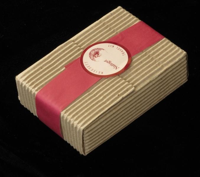 Liten uåpnet  pakke, med bølgepapp og rødt bånd rund. Inneholder sannsynligvis såpe, tannbørste og muligens tannkrem m.m.