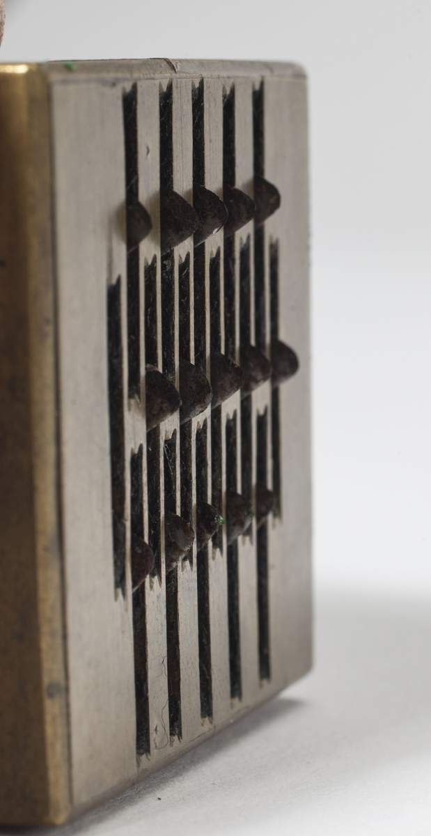 Apparat med 16 små kniver og en spennemekanisme til å lage 16 små blødende sår i huden. Apparatet er dekorert med blomstermotiv og geometriske mønster.